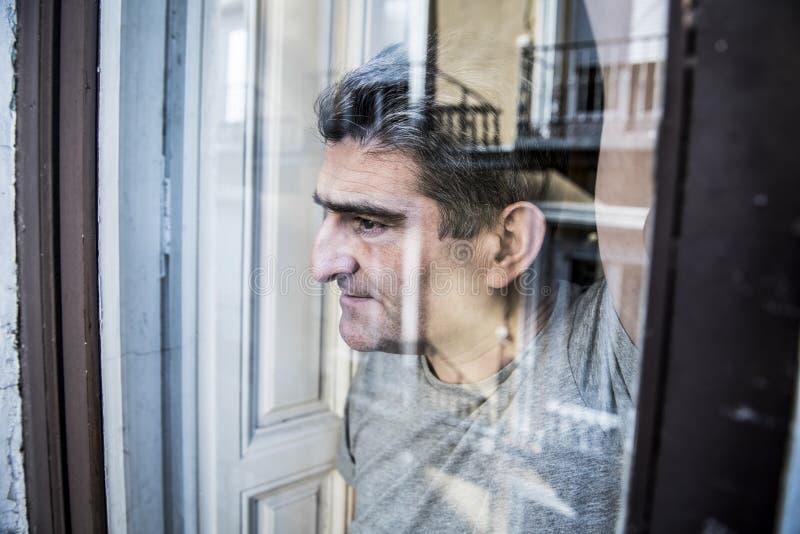 Schließen Sie herauf Porträt des traurigen und deprimierten Mannes 40s, der durch w schaut stockbild