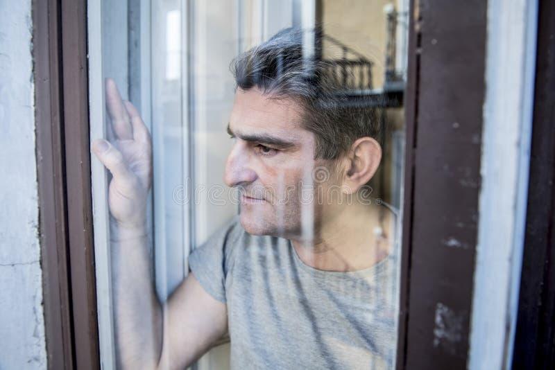 Schließen Sie herauf Porträt des traurigen und deprimierten Mannes 40s, der durch w schaut stockfotos