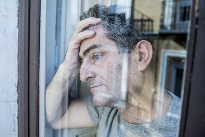 Schließen Sie herauf Porträt des traurigen und deprimierten Mannes 40s, der durch w schaut lizenzfreies stockbild