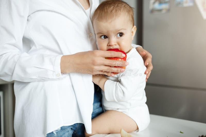 Schließen Sie herauf Porträt des unschuldigen kleinen Babys, das auf Tabelle in der Küche sitzt, beiseite schaut und roten Apfel  stockfotos