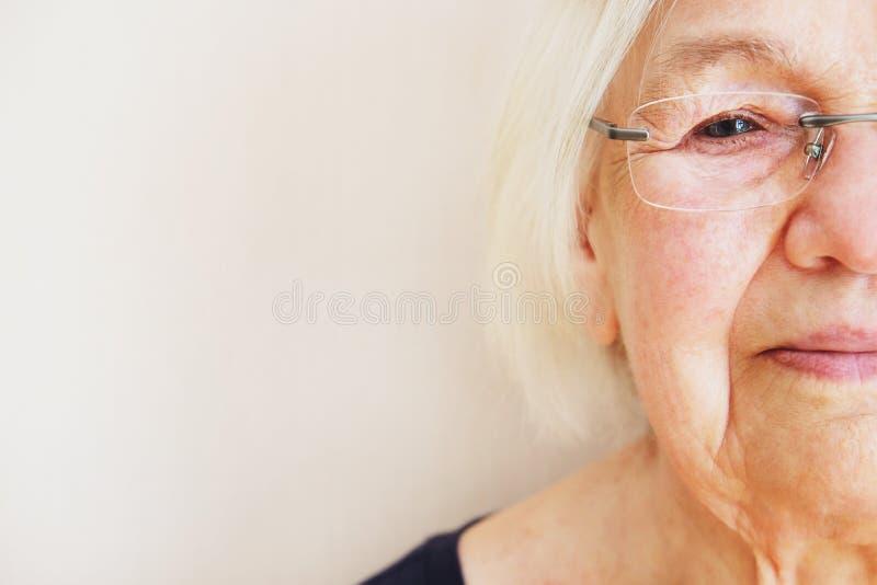 Schließen Sie herauf Porträt einer älteren Frau in den Brillen Halbe Frau der Gesichtsälteren personen Augenkrankheitskonzept stockfotografie