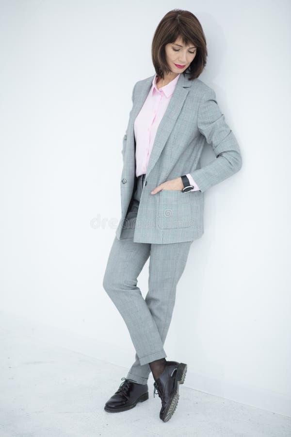Schließen Sie herauf Porträt einer ernsten Geschäftsfrau in der grauen Klage, die in der Stadt steht stockfotos