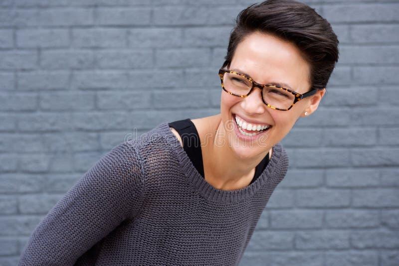 Schließen Sie herauf Porträt einer jungen Frau, die mit Gläsern lacht stockfoto
