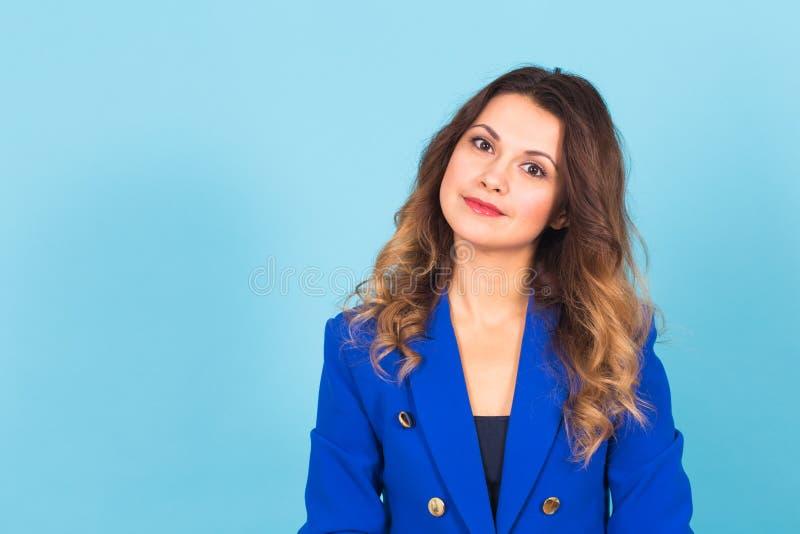Schließen Sie herauf Porträt einer schönen jungen Frau, die auf blauem Hintergrund lächelt stockfotografie