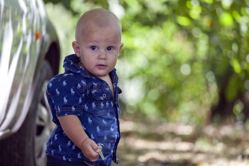 Schließen Sie herauf Porträt eines süßen kleinen Jungen, der den Schlüssel in seinem h hält stockfoto