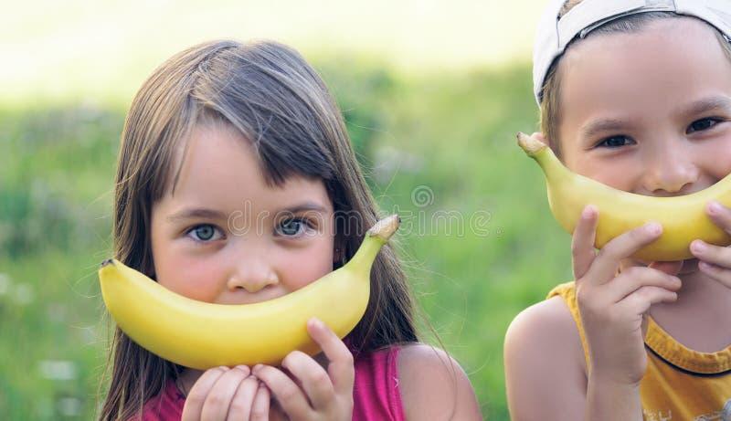 Schließen Sie herauf Porträt eines schönen jungen kaukasischen Mädchens und des Jungen mit Bananenlächeln auf Naturhintergrund lizenzfreie stockfotos