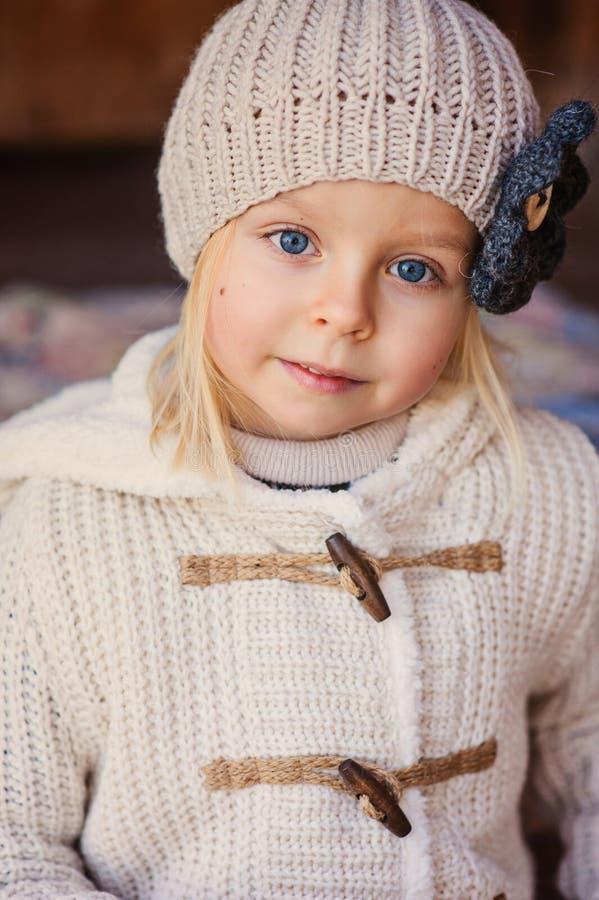 Schließen Sie herauf Porträt im Freien des entzückenden lächelnden Kindermädchens in der beige Strickmütze und im Mantel stockbild