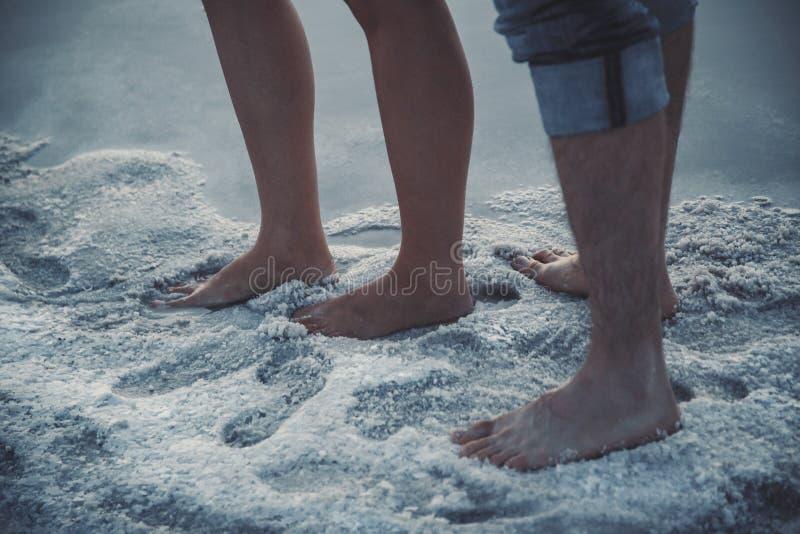 Schließen Sie herauf Porträt von Füßen, Beine von den Paaren, die nahe zum Salzsee im Salz stehen lizenzfreie stockfotografie