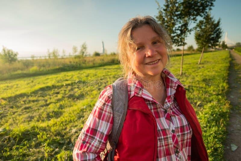 Schließen Sie herauf Porträt von glücklicher stehender Außenseite der älteren Frau im Sommer auf Feldhintergrund lizenzfreie stockbilder