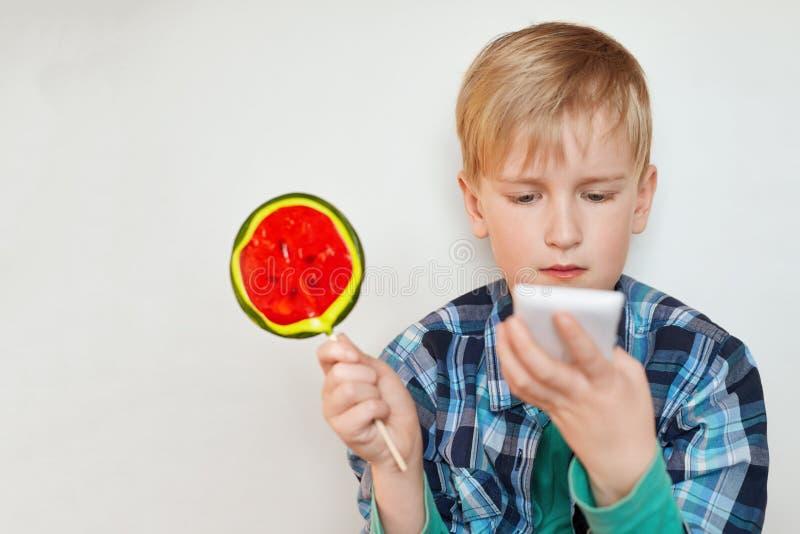 Schließen Sie herauf Profilbild des netten entzückenden kleinen Jungen mit dem hellen Haar und blauen den Augen, die süße Süßigke stockfotos
