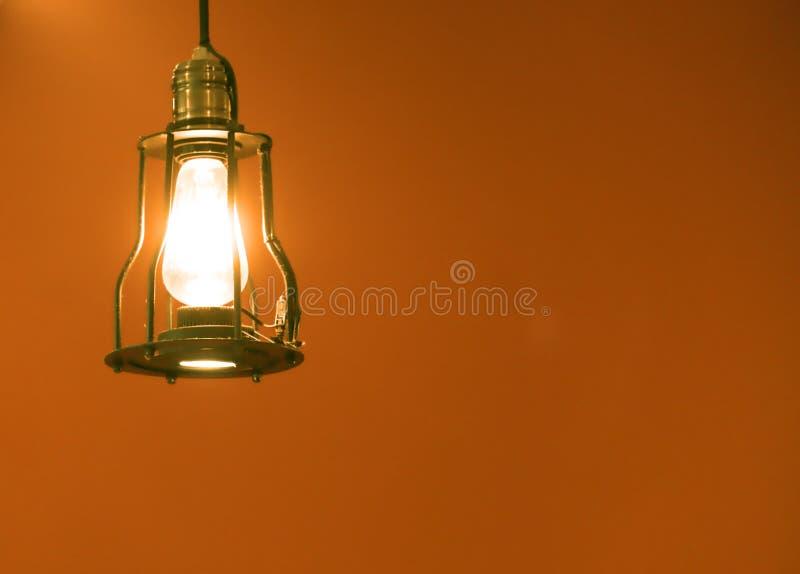 Schließen Sie herauf Retro- hängende helle Lampe, die Birne, die im orange Hintergrund dekorativ ist stockfotografie