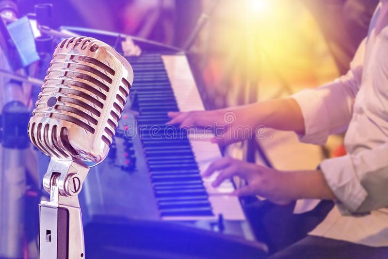 Schließen Sie herauf Retro- Mikrofon mit dem Musiker, der Tastatursynthesizer auf Band im Nachtkonzerthintergrund spielt lizenzfreies stockbild