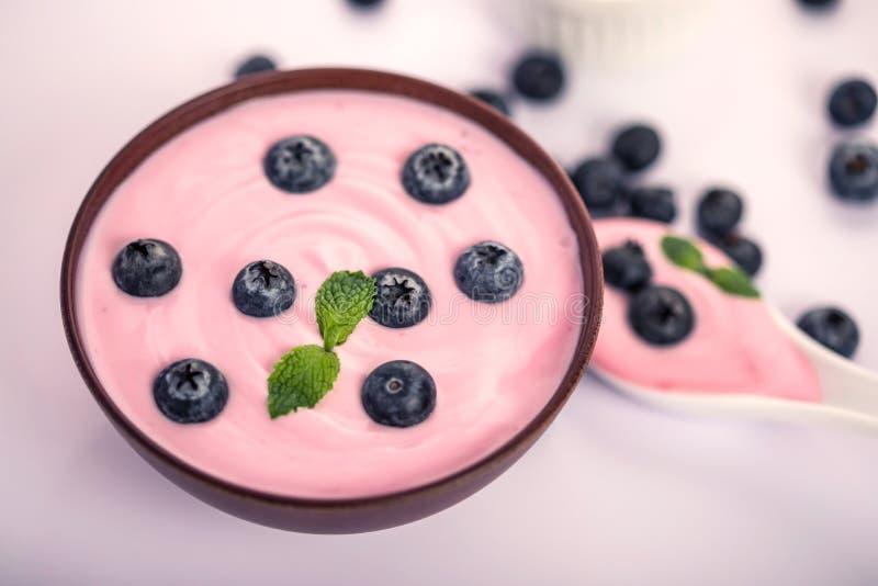 Schließen Sie herauf rosa sahnigen selbst gemachten Blaubeerfruchtjoghurt mit frischem grünem tadellosem Blatt auf weißem Hinterg stockbild