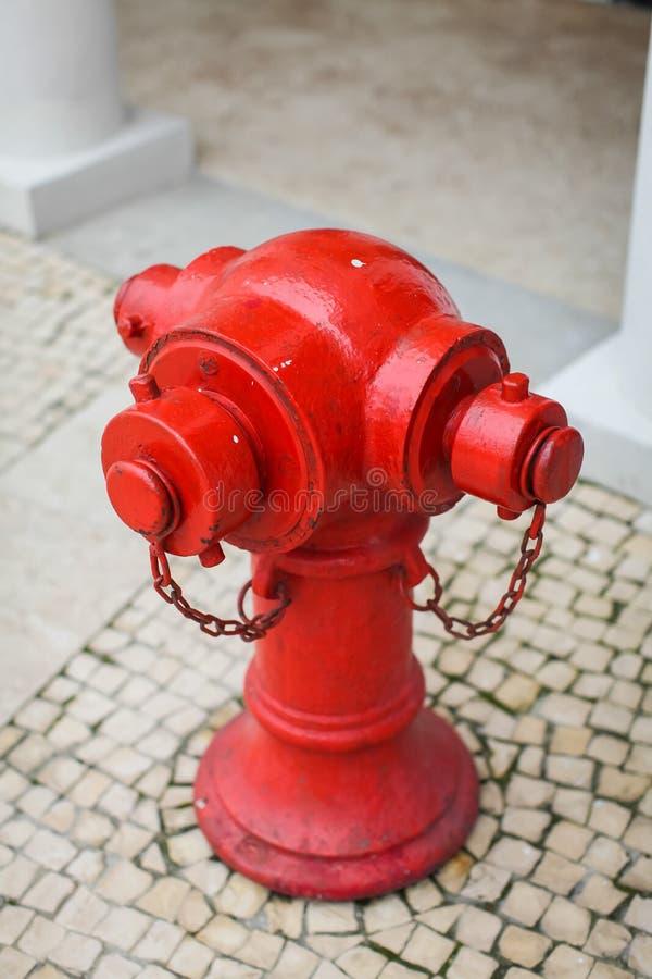 Schließen Sie herauf roten Hydranten im Schmutz auf Straße von Hong Kong auf Pflastersteinen lizenzfreie stockbilder