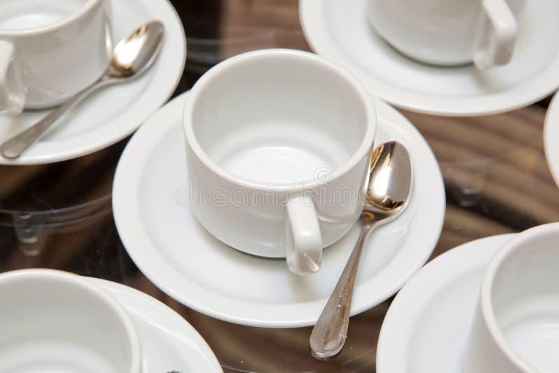 Schließen Sie herauf schmutzige Kaffeetasse- und Löffeleinstellung auf weißer Untertasse und Holztisch, nachdem Sie morgens in de stockbild