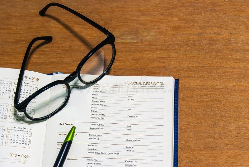 Schließen Sie herauf Schreibtisch mit Informationsseite des offenen Buches lizenzfreie stockbilder