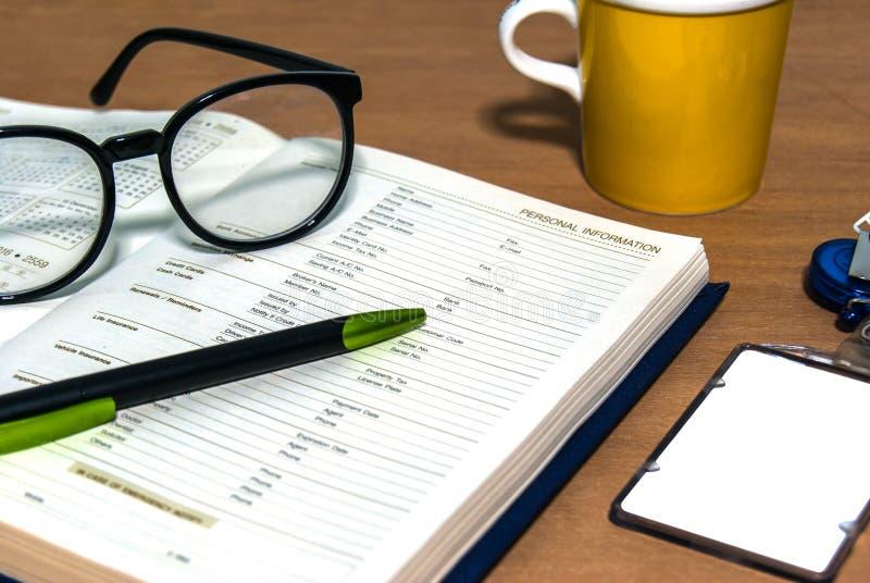 Schließen Sie herauf Schreibtisch mit Informationsseite des offenen Buches lizenzfreies stockfoto