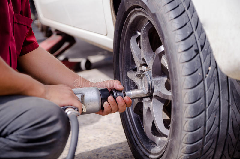 Schließen Sie herauf Schuss der Hände der Mechaniker, die pneumatischen Schlüssel t verwenden lizenzfreies stockbild