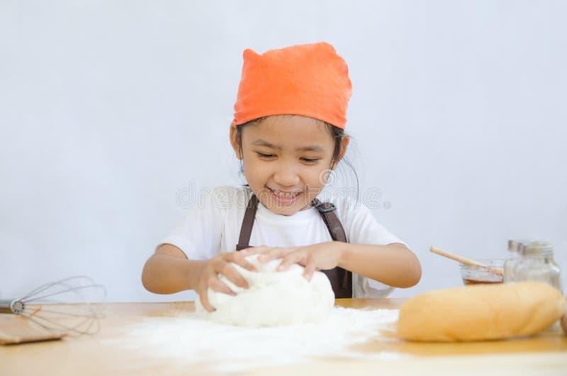Schließen Sie herauf Schuss des asiatischen kleinen Mädchens, das den Teig für die Herstellung knetet lizenzfreie stockfotografie