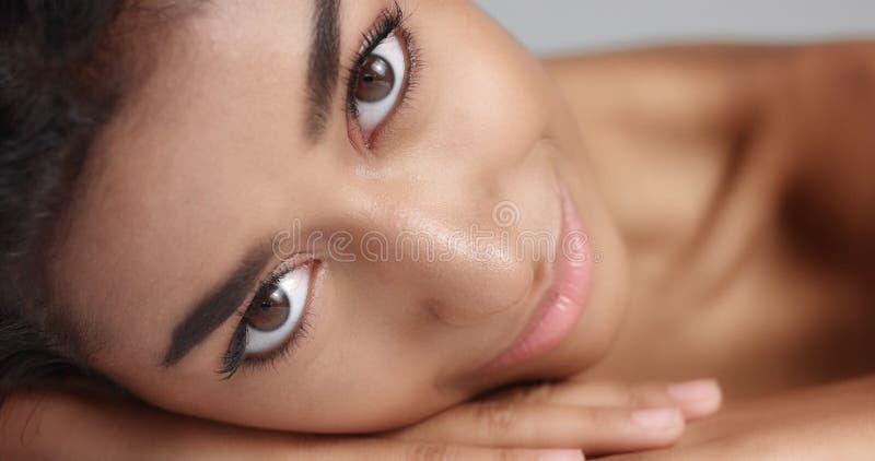 Schließen Sie herauf Schuss eines recht jungen wooman mit der glatten glühenden Haut, die auf einer weißen Massagetabelle sich en stockbild