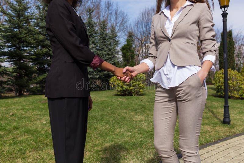 Schließen Sie herauf Schuss von zwei Geschäftsfrauen, die Hände rütteln Äußere der Frau stehende und tragende Geschäftskleidung stockfotos
