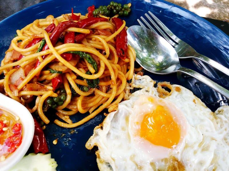 Schließen Sie herauf Spaghettis mit Basilikumspeck, getrocknetem Pfeffer des roten Paprikas und Spiegelei mit Gabel Löffelamerika lizenzfreies stockbild