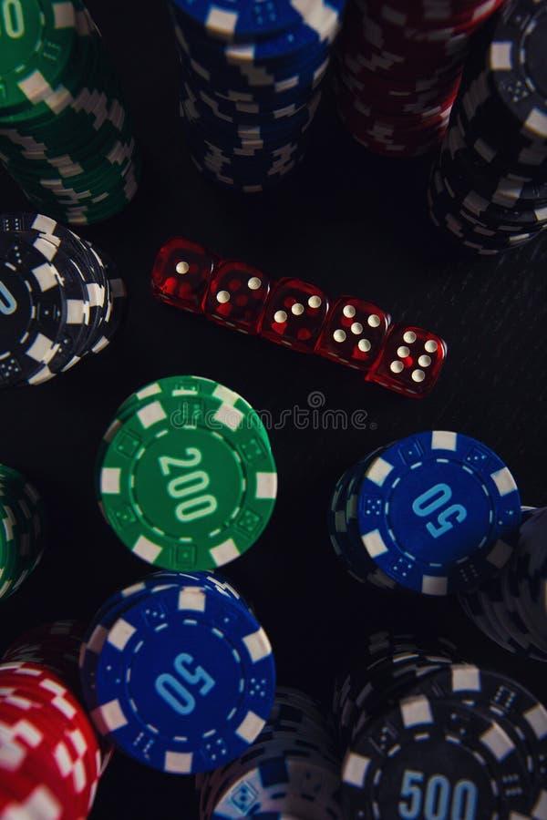 Schließen Sie herauf Stapel der verschiedenen farbigen Pokerchips und spielend würfelt auf der Kasinotabelle, die über schwarzem  lizenzfreie stockfotos