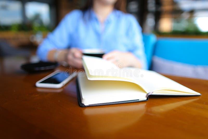 Schließen Sie herauf Tagebuch nahe Smartphone mit Studentin am Café im Hintergrund, unscharfes Foto lizenzfreie stockbilder