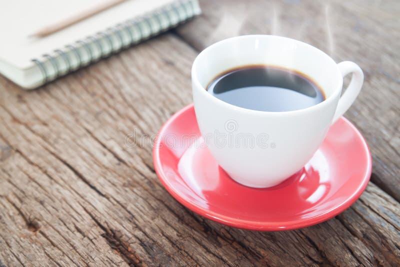 Schließen Sie herauf Tasse Kaffee auf rustikalem Holztisch, Lebensstilkonzept lizenzfreie stockfotos