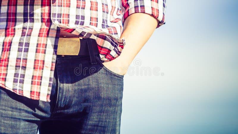Schließen Sie herauf tragende Jeans des Mannes mit der Hand auf Hüfte stockfotografie