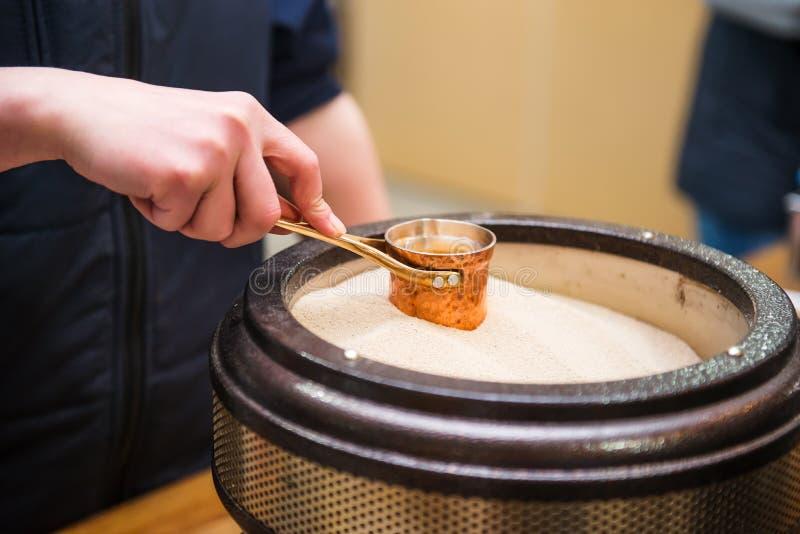 Schließen Sie herauf Vorbereitung des türkischen Kaffees im cezve im Sand an der Cafébar Berufs-barista Hand, die Kaffee in der T stockfoto