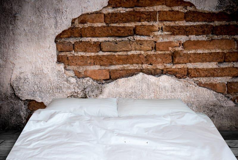 Schließen Sie herauf weiße Bettwäscheblätter und -kissen auf Natursteinwand r stockfotografie