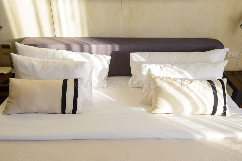 Schließen Sie herauf weiße Bettwäscheblätter und -kissen im Hotelzimmer lizenzfreie stockfotografie