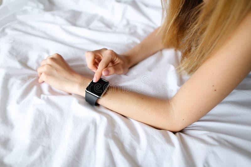 Schließen Sie herauf weibliche Hände mit intelligenter Uhr im weißen Leinenhintergrund stockbilder