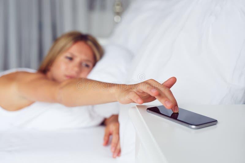 Schließen Sie herauf weibliche Handdösende Warnung am Handy stockfoto