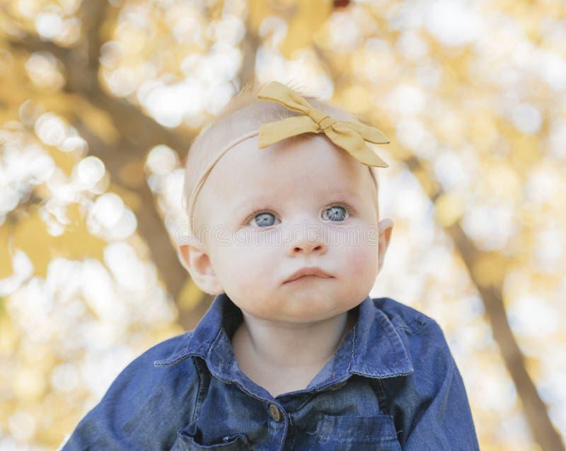 Schließen Sie oben auf Baby mit Bogen auf den Haupt- und enormen blauen Augen stockbilder