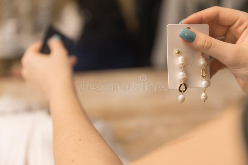 Schließen Sie oben auf dem Foto, das Mädchen zahlt mit einer Karte im Speicher für Ohrringe stockbild