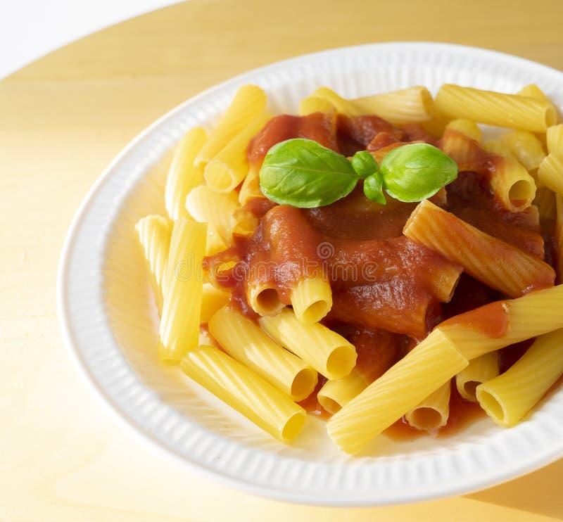 Schließen Sie oben auf dem Teller mit Makkaroni und Tomatensauce lizenzfreie stockfotos