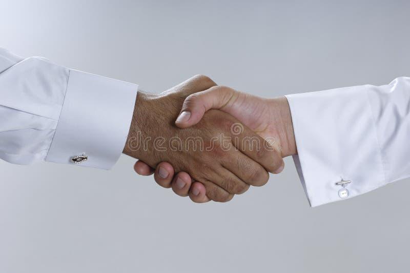 Schließen Sie oben auf den Geschäftsmännern, die Thob und Handdas rütteln tragen lizenzfreie stockfotos