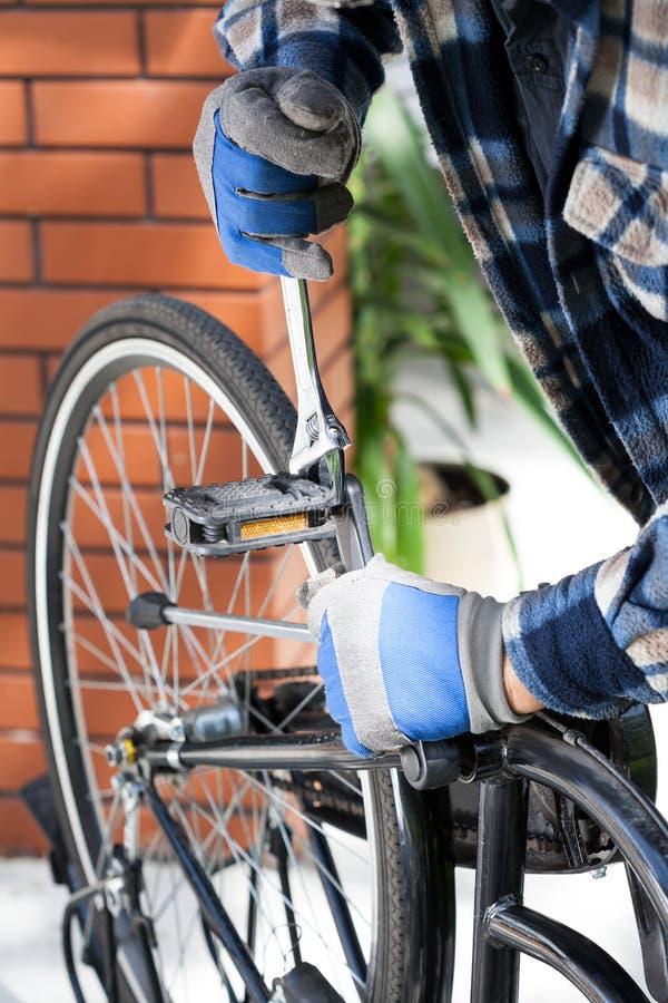 Schließen Sie oben auf der Hand des Mannes, die ein Fahrrad repariert stockbilder