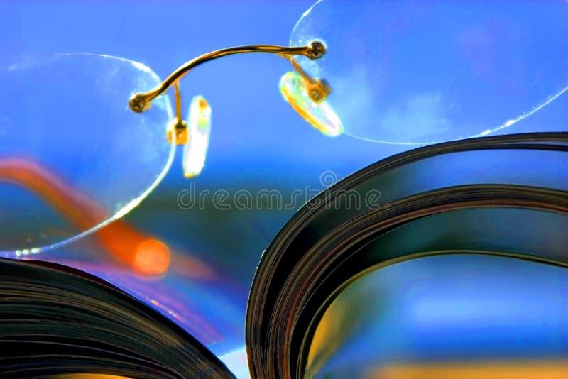 Schließen Sie oben auf einem Paar der Gläser und der Zeitschrift stockfotografie