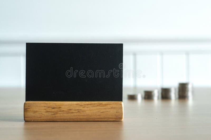 Schließen Sie oben auf einer Tafel mit Münzengeld im Hintergrund Leerer oder leerer Raum für Textnachricht lizenzfreie stockbilder