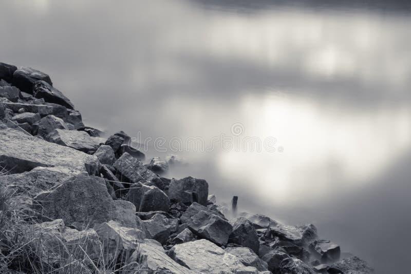 Schließen Sie oben auf Felsen auf Ufer mit dem Sonnenlicht des bewölkten Himmels, das im Wasserozean im Schwarzweiss-Sepiahinterg stockfoto