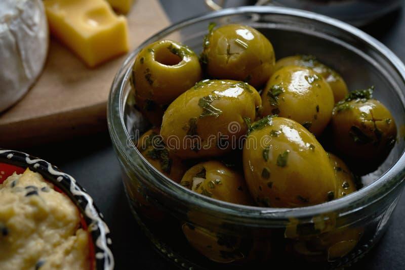 Schließen Sie oben auf Glasschüssel mit Oliven mit Petersilie auf schwarzer Tabelle lizenzfreie stockfotografie