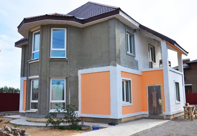Schließen Sie oben auf Malerei und dem Vergipsen der Außenhausmauer Fassaden-Wärmedämmung- und -malereiarbeiten lizenzfreies stockfoto