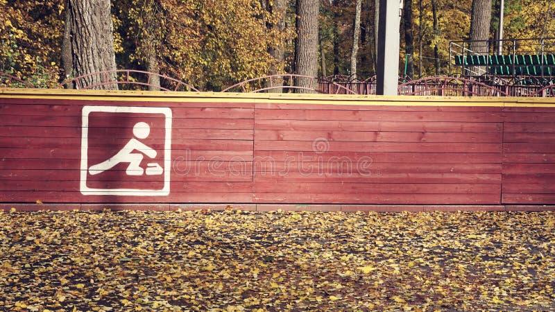 Schließen Sie oben auf weißem Fahrradzeichen oder Ikone und farbiges Zeichen der olympischen Ringe auf einem braunen Bretterzaun  lizenzfreies stockbild