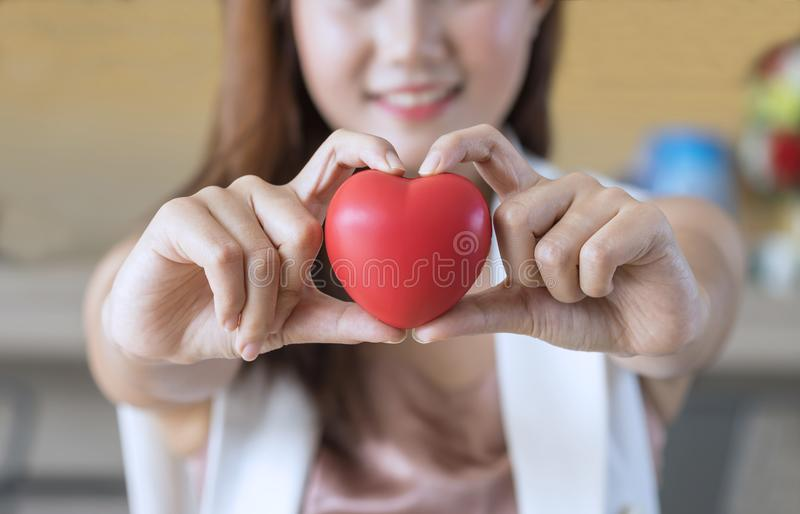 Schließen Sie oben, die Frau, die rotes Herz in den Händen hält lizenzfreies stockbild