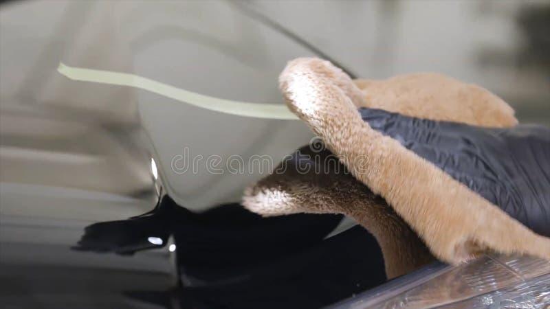 Schließen Sie oben für Mannhand im schwarzen Handschuh, der ein Autofenster in einer Waschanlage wäscht und Service säubern t?tig stockfotos