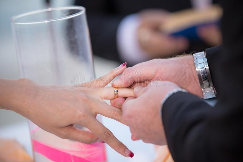 Schließen Sie oben an Hand von Bräutigam gesetztem an Verlobungsring auf dem Finger der Braut lizenzfreie stockfotografie