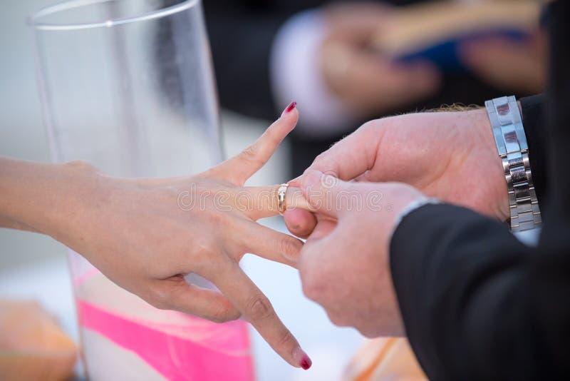 Schließen Sie oben an Hand von Bräutigam gesetztem an Verlobungsring auf dem Finger der Braut lizenzfreies stockfoto